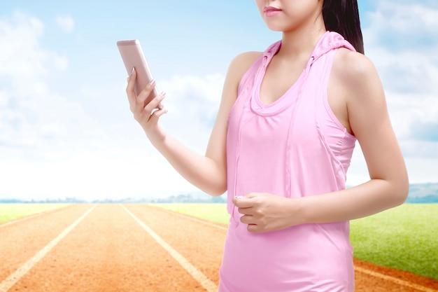 Asiatische läuferfrau, die einen handy an der pause nachdem dem laufen auf der laufbahn verwendet