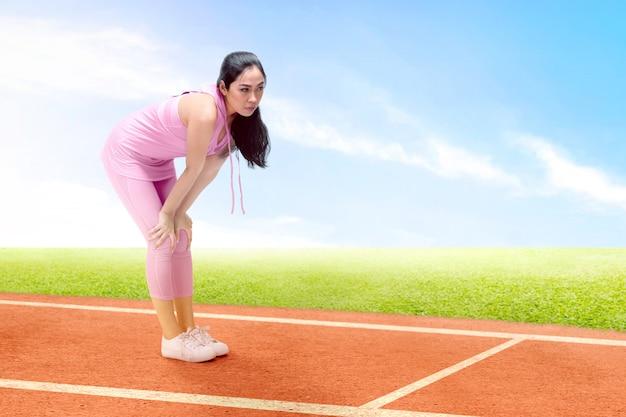 Asiatische läuferfrau machen eine pause, nachdem sie auf der laufbahn gelaufen ist
