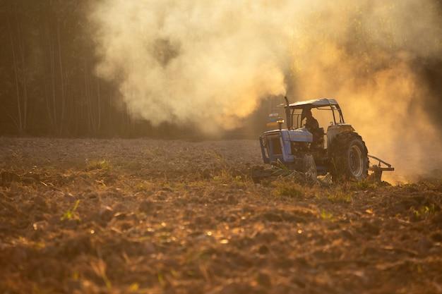 Asiatische landarbeiter benutzen traktoren, um den boden für das pflanzen vorzubereiten.
