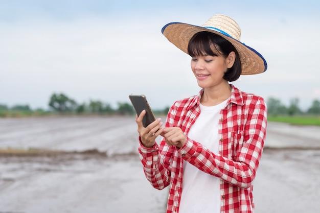 Asiatische landwirtin, die smartphone-handy an reisfarm verwendet