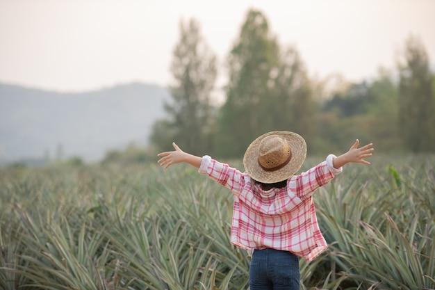 Asiatische landwirtin sieht wachstum der ananas in der farm, junges hübsches bauernmädchen, das auf ackerland mit den armen steht, die freudiges begeistertes glück erhoben.
