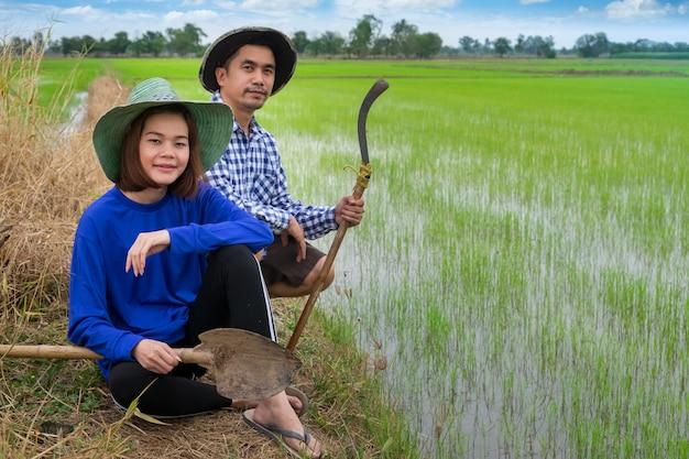 Asiatische landwirtpaare halten die werkzeuge, die im reisbauernhof bei thailand sitzen
