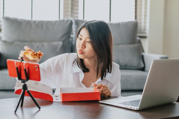 Asiatische lebensmittel-bloggerin, die pizza isst, während sie neues smartphone für ihren kanal unter verwendung des smartphones erstellt
