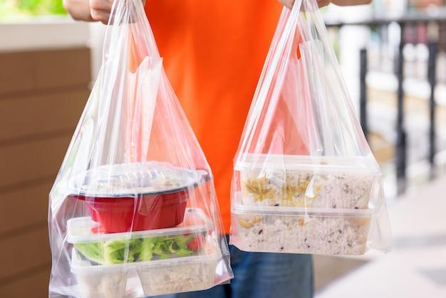 Asiatische lebensmittelboxen in plastiktüten, die vom zusteller in orangefarbener uniform an den kunden zu hause geliefert werden