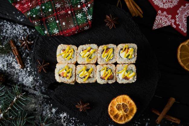 Asiatische lebensmittellieferung nach hause, verschiedene sushi-sets in plastikbehältern mit saucen