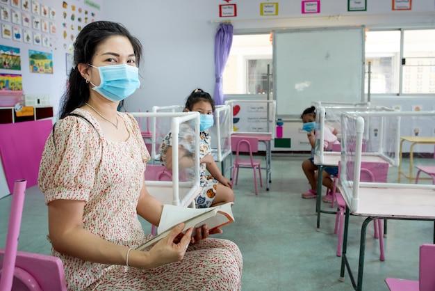 Asiatische lehrer und schüler tragen eine maske im klassenzimmer und in der schule, die gerade beginnt
