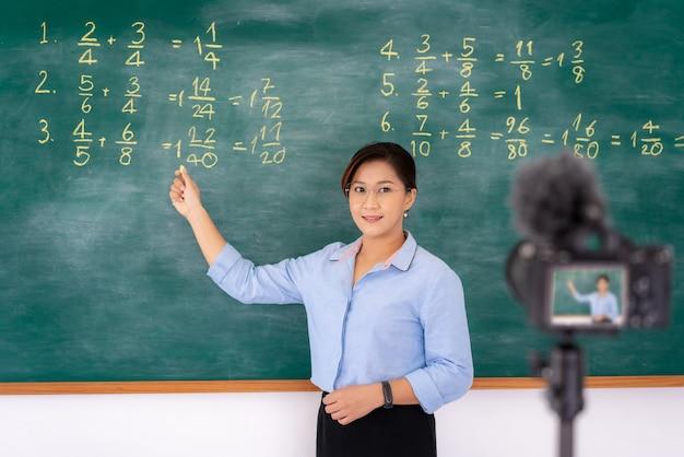 Asiatische lehrerin, die durch videokonferenz unterrichtet
