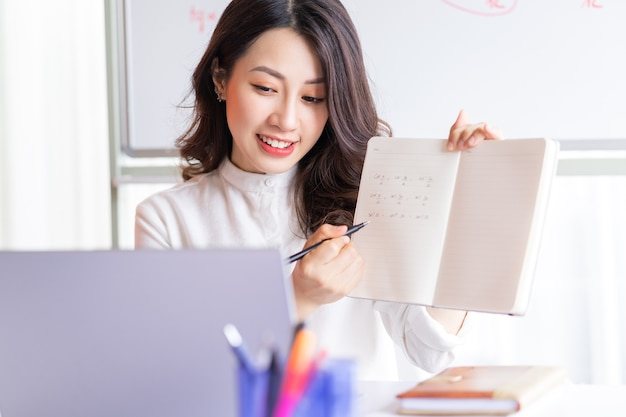 Asiatische lehrerin, die online zu hause unterrichtet