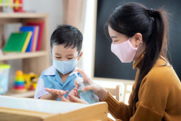 Asiatische lehrerin verwendet alkoholgel an der hand ihres schülers, um zu verhindern, dass viren im klassenzimmer in der vorschule auftreten.