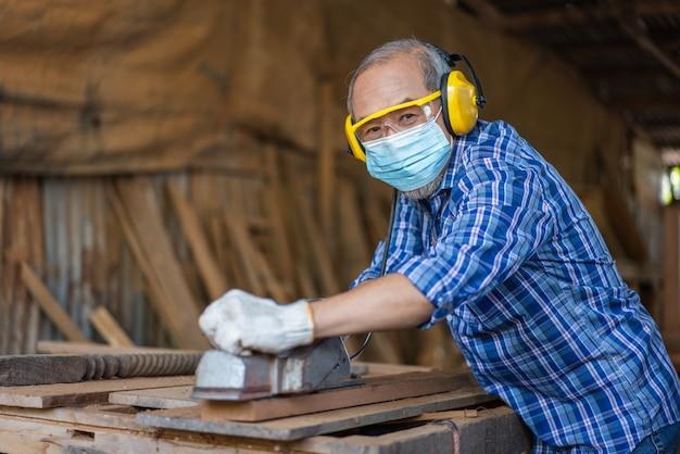 Asiatische leitende zimmermann tragen hygienemaske schützen mit elektrischen hobel justieren oberfläche auf holzbrett in der tischlerwerkstatt