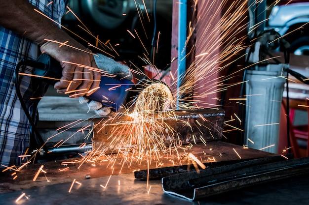 Asiatische leute benutzen das elektrische rad, das auf stahlkonstruktion in der fabrik reibt.
