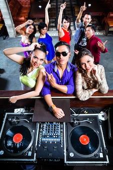 Asiatische leute, die auf tanzfläche im nachtklub feiern