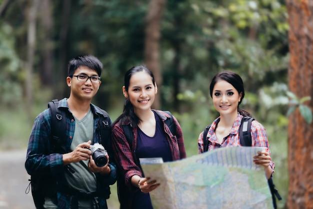 Asiatische leute, die mit rucksäcken wandern und karte schauen wandern