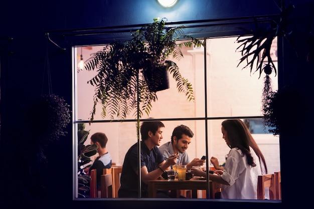 Asiatische leute, die party in einem restaurant mit freunden essen. in der nacht