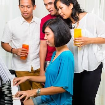 Asiatische leute, die zusammen am klavier sitzen