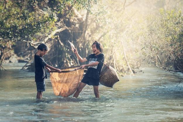 Asiatische mädchen, die am fluss fischen