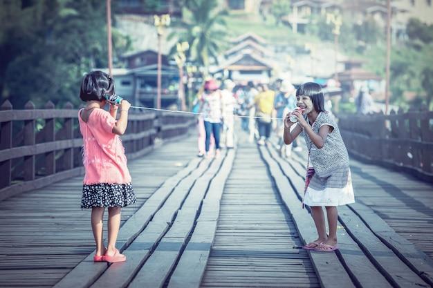 Asiatische mädchen, die an einem dosentelefon sprechen