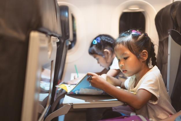 Asiatische mädchen, die mit dem flugzeug reisen und während des fluges ein buch lesen