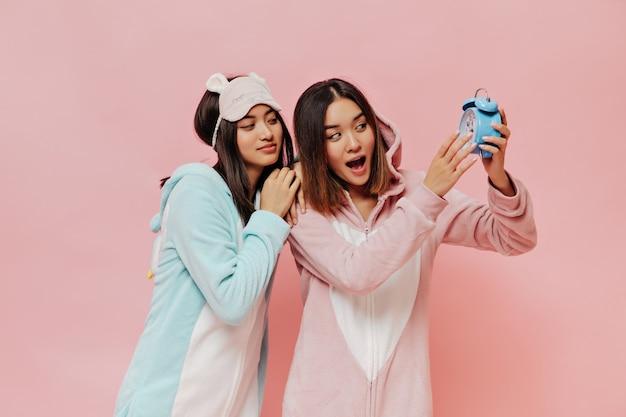 Asiatische mädchen in bunten süßen pyjamas schauen auf blauen wecker