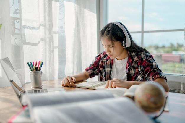 Asiatische mädchen lernen zu hause online. aufgrund der epidemischen lage der covid-19-virus-epidemie.