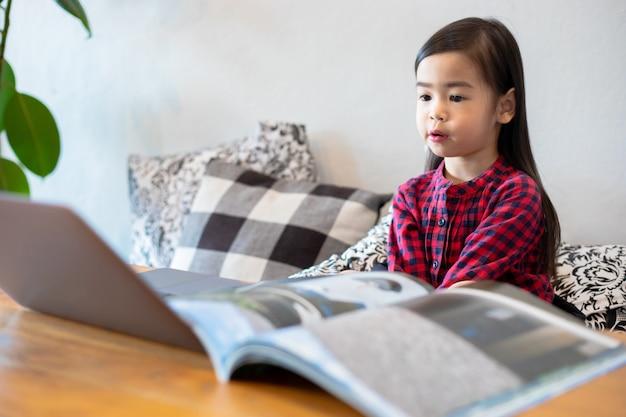 Asiatische mädchen oder töchter nutzen notizbücher und technologie zum online-lernen während der schulferien und zum anschauen von cartoons zu hause. bildungskonzepte und aktivitäten der familie
