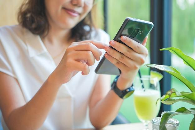 Asiatische mädchen spielen smartphone für unterhaltung und arbeit außerhalb des büros