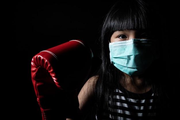 Asiatische mädchen tragen gesichtsmasken zum schutz vor viren und boxhandschuhe, um den kampf gegen viren als coronavirus zu symbolisieren