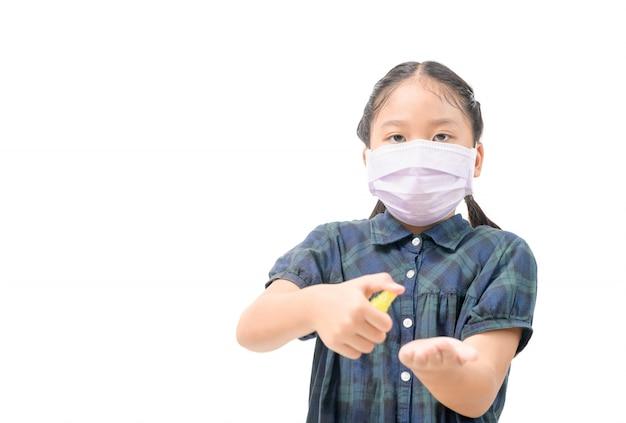 Asiatische mädchen tragen hygienemaske und drücken alkoholspray auf ihre hand oder schützen coronavirus