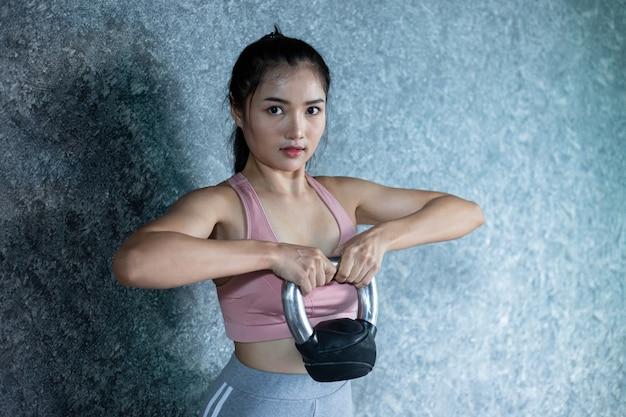 Asiatische mädchen trainieren mit der kettlebell im fitnessstudio.