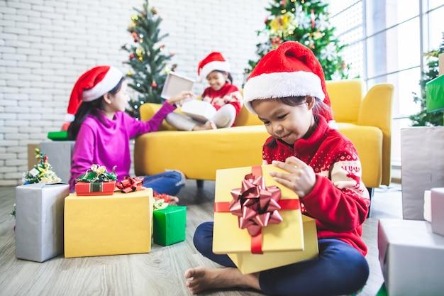 Asiatische mädchen überraschen mit geschenken und helfen, gemeinsam zu dekorieren, um im weihnachtsfest zu feiern