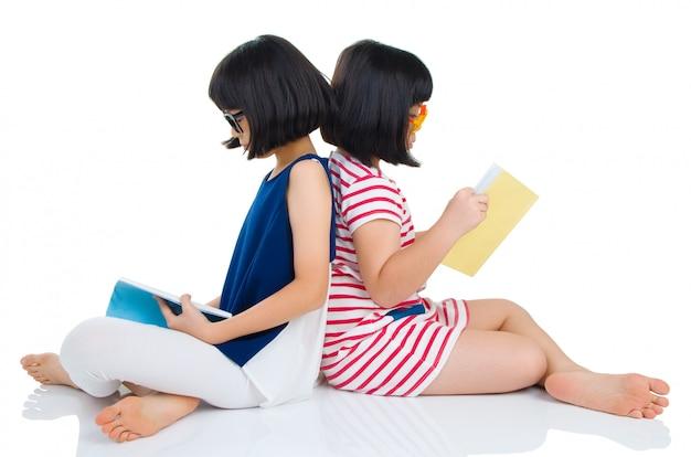 Asiatische mädchen, welche die schauspiele sitzen auf dem boden mit büchern tragen