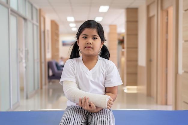 Asiatische mädchenbehandlung im krankenhaus liegend auf dem bett, das mit gebrochenem arm zurück von der operation verletzt.