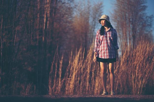 Asiatische mädchenfotos mit natürlichem gras und himmel, entspannen sich bei sonnenuntergang