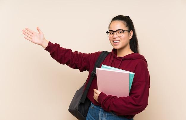 Asiatische mädchenfrau des jungen studenten über ausdehnungshänden der lokalisierten wand zur seite für die einladung zu kommen