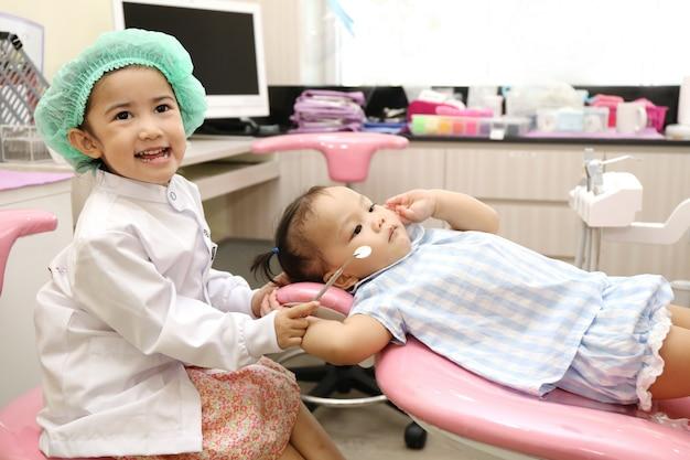 Asiatische mädchengruppe benutzen zahnarztausrüstung, um zahn für zahnschmerzen und gutes gesundes zu säubern