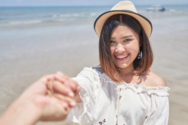 Asiatische mädchenholdinghand ihres freundes auf dem strand