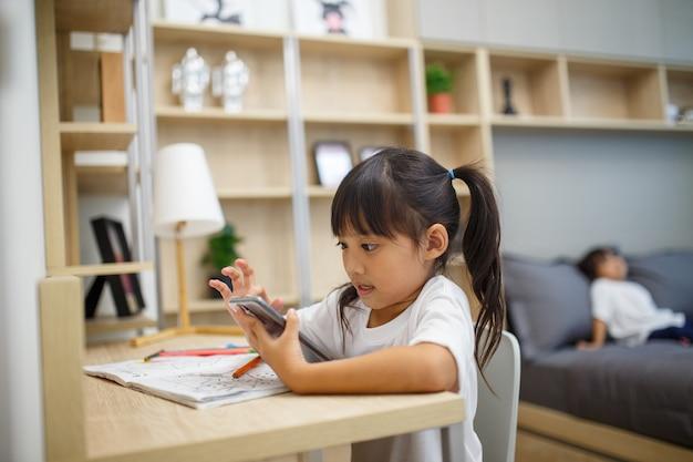 Asiatische mädchenstudentin online-lernklasse studieren sie online-videoanruf-zoom-lehrer, glückliches mädchen lernt englisch online mit laptop zu hause.neue normalität.covid-19-coronavirus.soziale distanzierung.bleiben sie zu hause