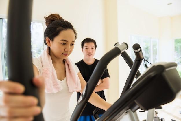Asiatische mädchenübung in der turnhalle mit trainer