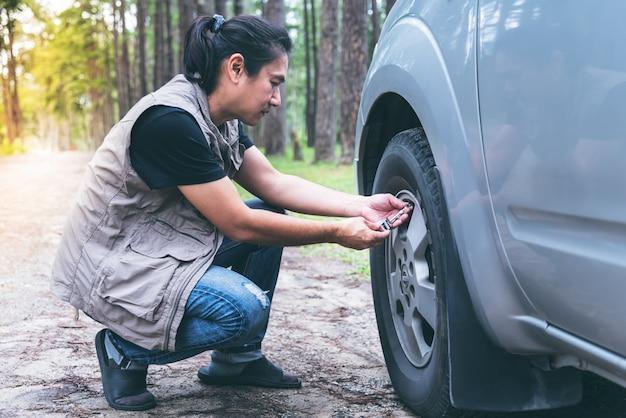 Asiatische männer benutzen kleine ausrüstung überprüfen sie den reifendruck-pickup, um für lange fahrten geeignet zu sein