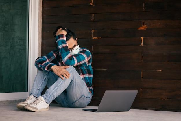 Asiatische männer, die berufstätig sind, tragen schutzmasken, die vor arbeitslosigkeit zu hause gestresst sitzen. konzept der wirtschaftskrise, arbeitslosigkeit der menschen und produktion der coronavirus-krankheit 2019 oder covid-19.