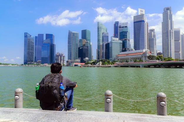 Asiatische männer, die einen rucksack tragen, sitzen am fluss und schauen auf das gebäude im zentrum des geschäfts in der großstadt.