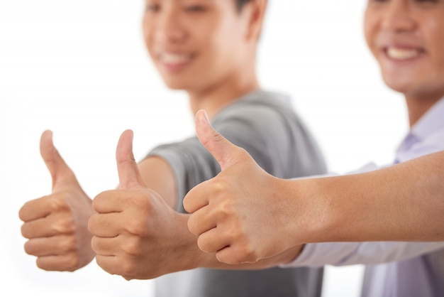 Asiatische männer, die sich zusammen händen anschließen und sich daumen zeigen