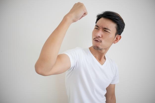 Asiatische männer, die weiße t-shirts tragen faust in der rechten hand heben zeichen der freude zeigend.