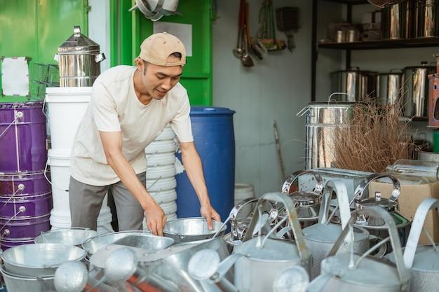 Asiatische männer halten einen eimer, während sie die vielen eimer im haushaltsgeräte-laden anordnen