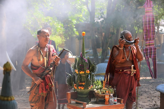 Asiatische männer im gebürtigen traditionellen kostüm, das durch erntezeremoniesatz sitzt