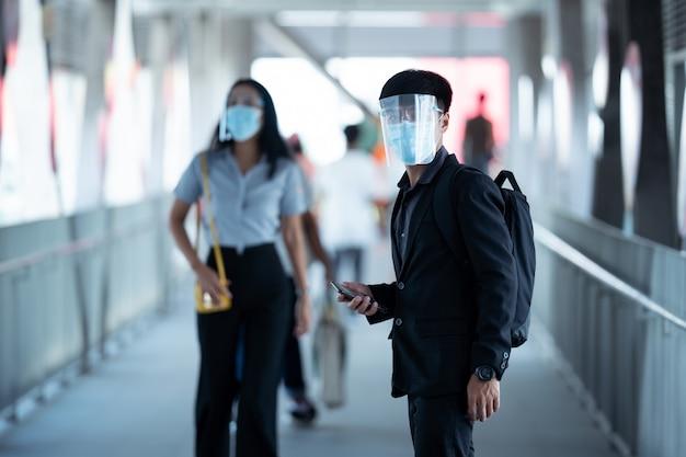 Asiatische männer kommen zur arbeit. sie tragen einen gesichtsschutz und eine antivirenmaske. sie sind am skywalk.