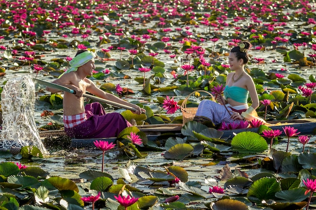 Asiatische männer sammeln rote lotosblumen, damit asiatische frauen anbeten. die kultur der thailänder.