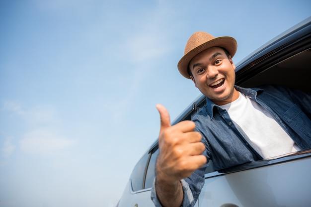 Asiatische männer tragen hüte und blaues hemd fährt und daumen hoch.