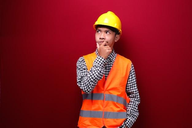 Asiatische männer tragen kontraktoruniform und schutzhelm mit ausdruck auf der suche nach ideen