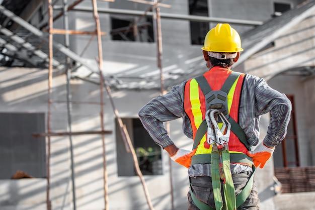 Asiatische männer tragen sicherheitskleidung bauarbeiterhelme und warnwesten auf baustellen